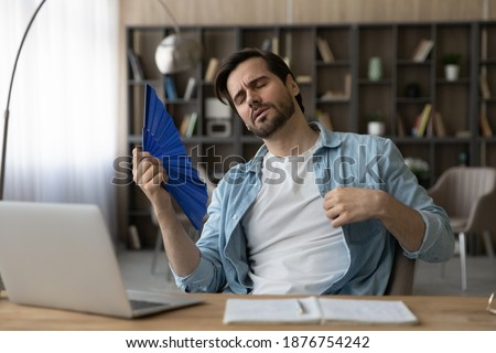Exhausted millennial Caucasian male employee sit at desk at home office feel overheated use waver. Tired young man breathe fresh air wave with hand fan, suffer from hot weather or lack or AC. Stockfoto ©