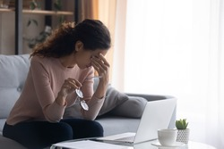 Exhausted millennial caucasian woman taking off eyeglasses, suffering from dry eyes syndrome from long computer overwork at home. Tired young female freelancer having problem with blurred eyesight.