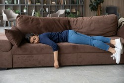 Exhausted millennial Indian woman lying on sofa in living room sleep or take nap. Tired young mixed race ethnicity female renter doze off fall asleep on couch at home. Tiredness, fatigue concept.