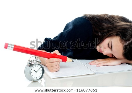 Exhausted schoolgirl dozing off while writing her test paper