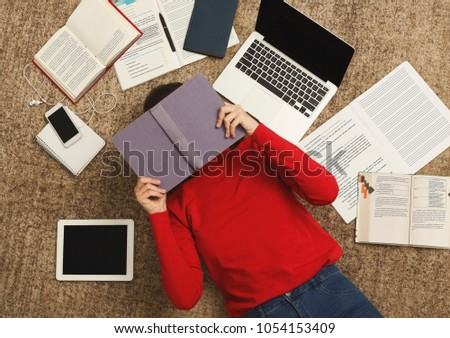 Exhausted student girl lying on the floor among textbooks, tests and gadgets, copy space. Woman covering face with book, got tired while preparing for exams. Education and overworking concept