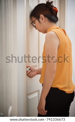 Exhausted, Tired Asian Business Beautiful woman in yellow shirt sleeping while opening the door at home. #741336673