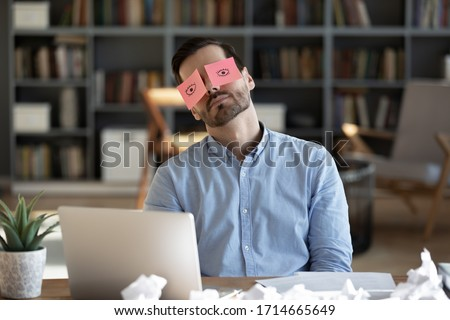 Exhausted tired businessman with painted eyes on stickers, adhesive notes on face sleeping at workplace, sitting at desk with laptop, unproductive lazy young male dozing, working on difficult project