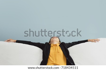 Exhausted, Tired, Lazy Asian Business woman in Yellow shirt and black suit sitting and sleepy on white sofa with blue wall and copy space. Stress from overtime working concept.