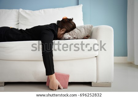 Exhausted, Tired, Lazy, sleepy Asian Business woman in black suit lying on white sofa with blue wall and copy space. Stress from overtime working concept.