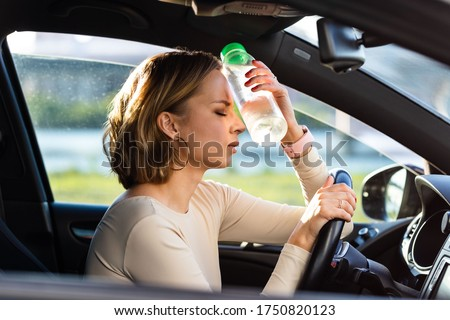 Exhausted woman driver feeling headache, sitting inside her car, applies a bottle of water to his forehead, hot weather. Stop after driving car in traffic jam. Blood pressure