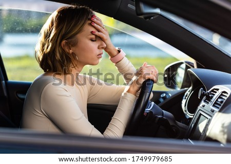 Photo of  Exhausted woman driver feeling headache, sitting inside her car, keeping hand to head and feeling anxiety. Stop after driving car in traffic jam.Blood pressure