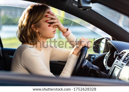 Exhausted woman driver feeling headache, sitting inside her car, keeping hand to head and feeling anxiety. Stop after driving car in traffic jam.Blood pressure