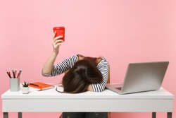 Exhausted woman laid her head down on the table holding cup of coffee or tea sit, work at white desk with pc laptop isolated on pastel pink background. Achievement business career concept. Copy space