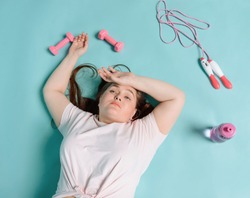Exhausted woman laying after workout, top view. Pink dumbbells, a jump rope and a bottle of water on blue background. Hard work to lose weight.