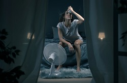 Exhausted woman suffering suring the heatwave, she is holding a water bottle and sitting in front of a cooling fan in the bedroom