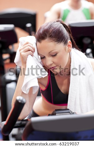 Exhausted woman wiping her face with a towel sitting on a cross trainer in a sport centre