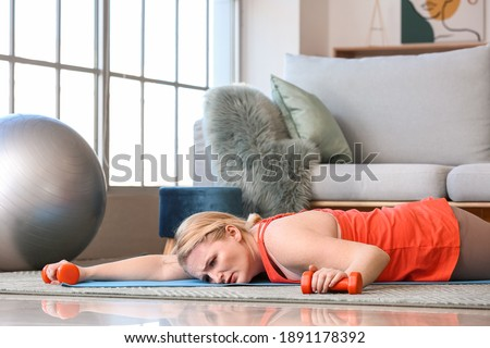 Exhausted woman with excess weight lying on floor after training at home Stock photo ©