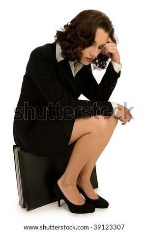 Exhausted young business woman sitting on large briefcase