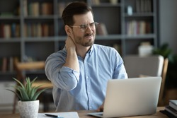 Exhausted young Caucasian male worker sit at desk massage neck suffer from strain spasm muscles. Tired unwell man overwhelmed with computer work sedentary lifestyle struggle with back pain or ache.