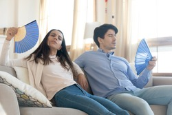 Exhausted young man and woman sit on couch at home breathe fresh air form waver, lack air conditioner, overheated couple rest on sofa suffer from heatstroke or hot weather, wave with hand fan