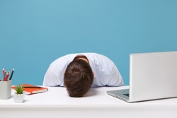 Exhausted young man in light shirt sit, work at desk with pc laptop isolated on pastel blue background. Achievement business career lifestyle concept. Mock up copy space. Laid his head down on desk