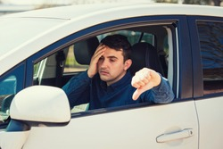 Exhausted young man sitting behind the steering wheel of the examination car showing thumb down gesture keeps hand to head feeling headache. Unlucky student guy failed the driver license exam.