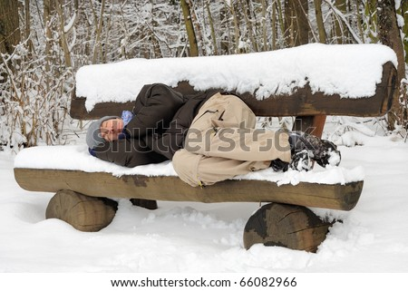 Exhausted young man sleeping on a snow-covered bench, ignoring the chill