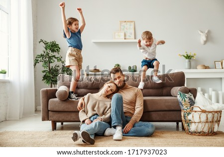Exhausted young parents sitting on floor and hugging while energetic kids having fun and jumping on sofa during weekend together at home  Stock photo ©