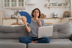 Exhausted young woman suffering from heatstroke flat without air-conditioner, waving blue fan, sitting on couch at home, working on laptop computer. Overheating, high temperature, hot summer weather.