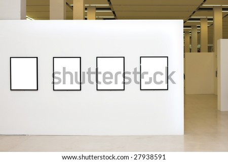 Exhibition in museum with four empty frames on white walls
