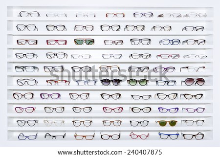 exhibitor of glasses consisting of shelves of fashionable glasses shown on a wall at the optical shop  #240407875