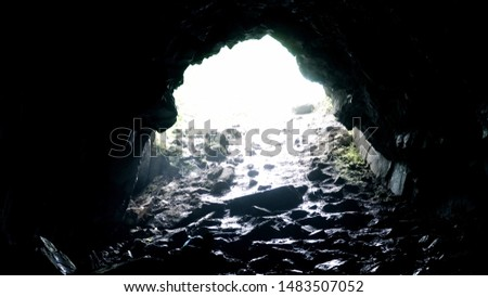 Exit from dark rocky cave. Stock footage. Bright light at exit of rocky cave covered with darkness in dampness. Dampness and moisture in caves in cloudy weather