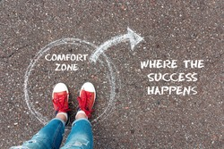 Exit from the comfort zone concept. Feet  in red sneakers standing inside circle comfort zone and outward arrow chalky on the asphalt.