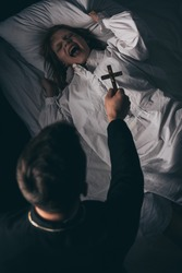 exorcist holding cross over obsessed yelling girl in bed