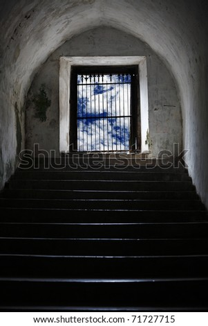 Exotic ancient staircase coming up  from an underground catacomb into a blue cloudy open space.