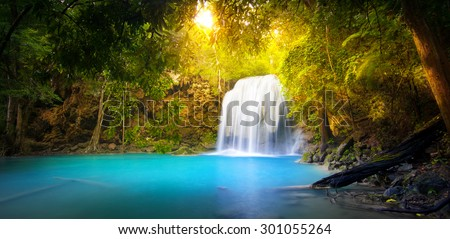 Exotic background of beautiful jungle forest with majestic waterfall falling into blue water lake and sun light rays shining through green leaves of tropical plants ant trees. Rainforest panorama stock photo