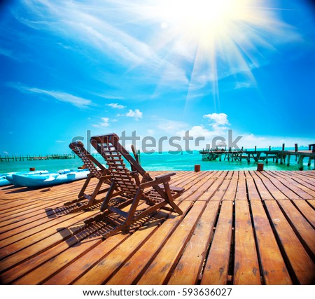 Shutterstock Exotic Beach, Paradise. Travel, Tourism and Vacations Concept. Landscape of Tropical Resort. couple of sun beds waiting for tourists. Jetty near Cancun, Mexico