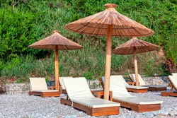 Exotic Beach with Umbrellas . Straw Umbrellas and Sun Loungers on the Pebble Beach