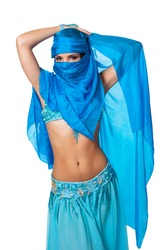 Exotic belly dancer peeking from behind a blue veil wrapped around her head and face. Isolated on white. Clipping path included.