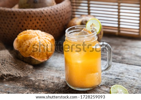 exotic fruit juice from Bel fruit or wooden Apple called in India Bel Ka Sharbat. cold fruit drink with ice and Bel fruit slices on wooden rustic background. natural detox. vitamins for immunity Сток-фото ©