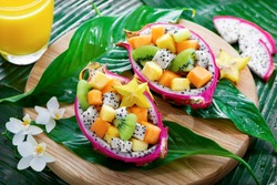 Exotic fruit salad served in half a dragon fruit on palm leaves with tropical flowers