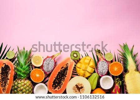 Exotic fruits and tropical palm leaves on pastel pink background - papaya, mango, pineapple, banana, carambola, dragon fruit, kiwi, lemon, orange, melon, coconut, lime. Top view