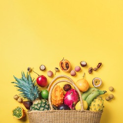 Exotic fruits in straw summer bag on yellow background. Top view. Copy space. Tropical fruits flat lay. Zero waste, plastic free concept. Travel and holiday concept. Vegan, vegetarian healthy diet