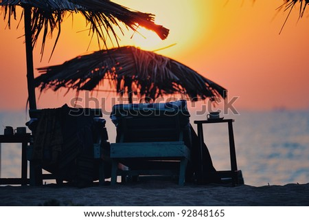 Exotic lean-to of palm leaves and deck chairs in sunset