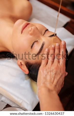 Exotic procedures. Attentive and gentle master touching forehead of her client and pressing fingers in special spot #1326630437