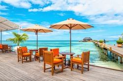 Exotic restaurant on the water, tables and chairs under sun umbrellas on the background of wooden bungalows