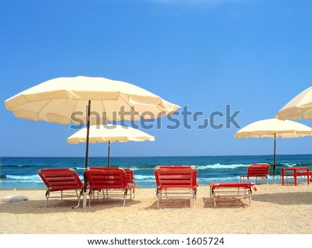 Exotic scene with parasols and red chairs near the ocean