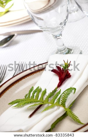 Exotic theme table setting. Arrangments with fresh fern and kangaroo paws flower