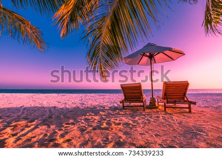 Exotic tropical beach sunset, colorful landscape for background or wallpaper. Romantic beach scene with chairs and soft sand. Design of tourism for summer vacation holiday destination concept. #734339233