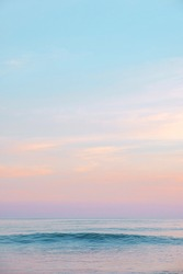 Expanse of the ocean against the sunset sky. Gorgeous pink, lilac sunset over the quiet expanse of the sea with wave. Fantastic seascape. Natural composition.