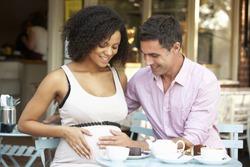 Expectant couple sitting outside cafe