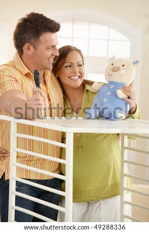 Expectant couple standing together looking at baby toy while putting up baby bed.