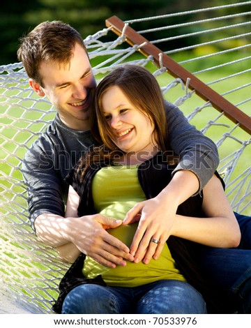 Expectant young couple on hammock, creating a heart on their soon to be child.
