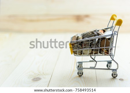 Expense, shopping and financial saving concept : Shopping cart / trolley and coins on a wood table, an image depicts saving money for personal finance or for shopping pleasure in special occasion. #758493514